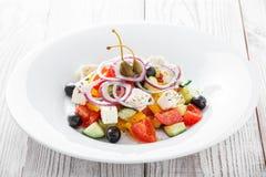 Ελληνική σαλάτα με τα φρέσκα λαχανικά, τις ελιές και το τυρί φέτας ξύλινο στενό σε επάνω υποβάθρου Στοκ Εικόνα