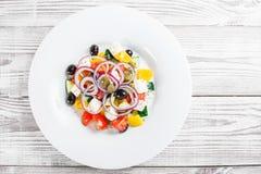Ελληνική σαλάτα με τα φρέσκα λαχανικά, τις ελιές και το τυρί φέτας ξύλινο στενό σε επάνω υποβάθρου Στοκ Φωτογραφία