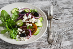 Ελληνική σαλάτα - σαλάτα με τις ντομάτες, τα αγγούρια, τις ελιές και το τυρί φέτας σε ένα άσπρο πιάτο Στοκ εικόνα με δικαίωμα ελεύθερης χρήσης
