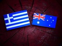 Ελληνική σημαία με την αυστραλιανή σημαία σε ένα κολόβωμα δέντρων που απομονώνεται Στοκ Φωτογραφία