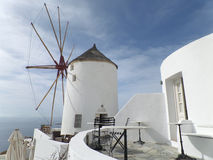 Ελληνικός ανεμόμυλος και αρχιτεκτονικές ύφους άσπρος στο φως του ήλιου απογεύματος, νησί Santorini της Ελλάδας Στοκ Εικόνα