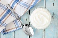Ελληνικό γιαούρτι, με το ύφασμα και το κουτάλι στο μπλε ξύλο Στοκ Φωτογραφία