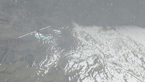 Ελικόπτερο που πετά πέρα από τα βουνά στο χιόνι απόθεμα βίντεο