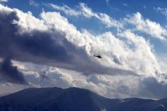Ελικόπτερο στα νεφελώδη βουνά ουρανού και χειμώνα Στοκ Φωτογραφία