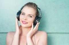 Ελκυστικά ακουστικά εκμετάλλευσης κοριτσιών που χαμογελούν και μουσική ακούσματος Στοκ Φωτογραφίες