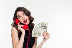 Ελκυστικά χαρούμενα σγουρά θηλυκά χρήματα εκμετάλλευσης και ομιλία στο τηλέφωνο στοκ εικόνες