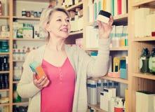 Ελκυστικές θηλυκές σειρές ξεφυλλίσματος πελατών των προϊόντων φροντίδας δέρματος Στοκ Εικόνα