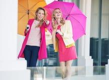 Ελκυστικές φίλες με τις ζωηρόχρωμες ομπρέλες στοκ εικόνες