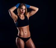 Ελκυστική αθλητική γυναίκα με τα μπλε εγκιβωτίζοντας περικαλύμματα στο μαύρο υπόβαθρο στο στούντιο Μαυρισμένο φίλαθλο κορίτσι Ένα Στοκ φωτογραφία με δικαίωμα ελεύθερης χρήσης