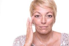 Ελκυστική ανώτερη ξανθή γυναίκα που ελέγχει τη χροιά της στοκ φωτογραφίες