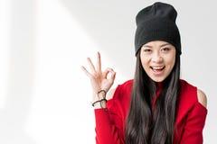 Ελκυστική ασιατική γυναίκα που κάθεται και που παρουσιάζει εντάξει σημάδι Στοκ Εικόνες