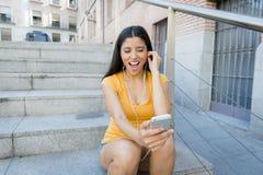 Ελκυστική λατινική γυναίκα που ακούει τη μουσική στο έξυπνο τηλέφωνό της Στοκ Φωτογραφία