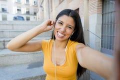 Ελκυστική λατινική γυναίκα που ακούει τη μουσική στο έξυπνο τηλέφωνό της Στοκ Φωτογραφίες