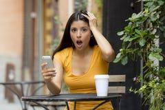 Ελκυστική λατινική γυναίκα που συγκλονίζεται στο έξυπνο τηλέφωνό της Στοκ Εικόνα
