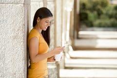 Ελκυστική λατινική γυναίκα στο έξυπνο τηλέφωνό της Στοκ Εικόνες