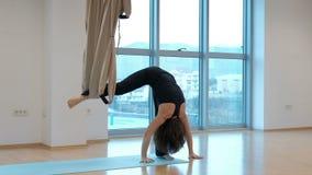 Ελκυστική γιόγκα βαρύτητας πρακτικών γυναικών στο στούντιο στο εσωτερικό απόθεμα βίντεο