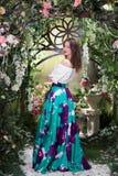 Ελκυστική γυναίκα μέσα στο floral κήπο μπλε φούστα Αφηρημένες ανασκοπήσεις φαντασίας με το μαγικό βιβλίο Στοκ Φωτογραφία