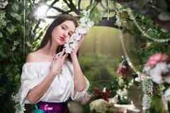 Ελκυστική γυναίκα μέσα στο floral κήπο μπλε φούστα Αφηρημένες ανασκοπήσεις φαντασίας με το μαγικό βιβλίο Στοκ εικόνες με δικαίωμα ελεύθερης χρήσης