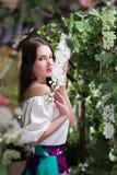 Ελκυστική γυναίκα μέσα στο floral κήπο μπλε φούστα Αφηρημένες ανασκοπήσεις φαντασίας με το μαγικό βιβλίο Στοκ Φωτογραφίες