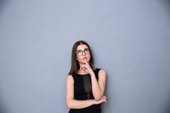 Ελκυστική γυναίκα με το δάχτυλο πέρα από τα χείλια που εξετάζει επάνω το copyspace Στοκ εικόνα με δικαίωμα ελεύθερης χρήσης