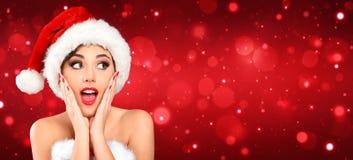 Ελκυστική γυναίκα με το καπέλο Santa που φαίνεται έκπληκτη στοκ εικόνα με δικαίωμα ελεύθερης χρήσης