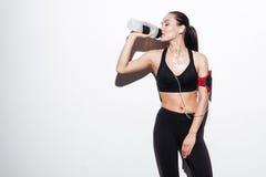 Ελκυστική γυναίκα με armband το πόσιμο νερό και άκουσμα τη μουσική Στοκ εικόνα με δικαίωμα ελεύθερης χρήσης