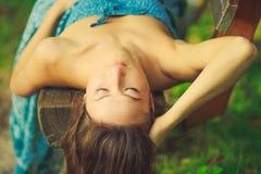 Ελκυστική γυναίκα που βάζει στον πάγκο στο δάσος Στοκ εικόνα με δικαίωμα ελεύθερης χρήσης