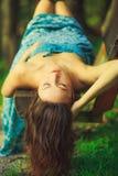 Ελκυστική γυναίκα που βάζει στον πάγκο στο δάσος Στοκ Φωτογραφίες
