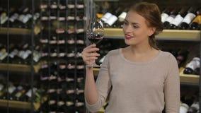 Ελκυστική γυναίκα που εξετάζει το χρώμα του κρασιού απόθεμα βίντεο