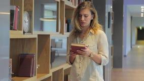 Ελκυστική γυναίκα που επιλέγει ένα βιβλίο από το ράφι απόθεμα βίντεο