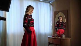 Ελκυστική γυναίκα που ελέγχει την κομψή εξάρτηση στον καθρέφτη απόθεμα βίντεο
