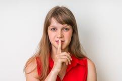 Ελκυστική γυναίκα που παρουσιάζει ένα δάχτυλο, που κάνει τη χειρονομία σιωπής στοκ εικόνες