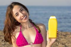 Ελκυστική γυναίκα που παρουσιάζει κρέμα ήλιων Στοκ φωτογραφία με δικαίωμα ελεύθερης χρήσης