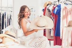 Ελκυστική γυναίκα που προσπαθεί σε ένα καπέλο Ευτυχείς θερινές αγορές στοκ εικόνες με δικαίωμα ελεύθερης χρήσης