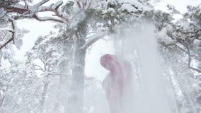 Ελκυστική γυναίκα που τινάζει τους χιονώδεις κλάδους φιλμ μικρού μήκους