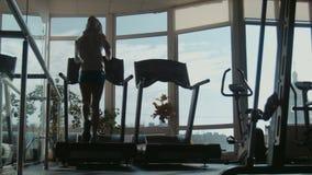 Ελκυστική γυναίκα που τρέχει treadmill στην αθλητική γυμναστική φιλμ μικρού μήκους