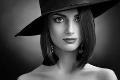 Ελκυστική γυναίκα που φορά μια τοποθέτηση καπέλων στο μαύρο υπόβαθρο στοκ εικόνες