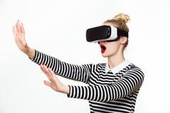 Ελκυστική γυναίκα που φορά τα προστατευτικά δίοπτρα εικονικής πραγματικότητας VR κάσκα Στοκ Φωτογραφία