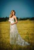 Ελκυστική γυναίκα που φορά την άσπρη μακροχρόνια τοποθέτηση φορεμάτων υπαίθρια Στοκ φωτογραφία με δικαίωμα ελεύθερης χρήσης