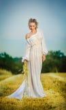 Ελκυστική γυναίκα που φορά την άσπρη μακροχρόνια τοποθέτηση φορεμάτων υπαίθρια Στοκ εικόνα με δικαίωμα ελεύθερης χρήσης