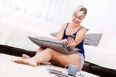 Ελκυστική γυναίκα που χρησιμοποιεί ένα έξυπνο τηλέφωνο στο καθιστικό. Στοκ Εικόνα