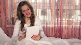 Ελκυστική γυναίκα που χρησιμοποιεί την ψηφιακή ταμπλέτα στο κρεβάτι στο σπίτι απόθεμα βίντεο