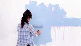 Ελκυστική γυναίκα που χρωματίζει τον τοίχο της φιλμ μικρού μήκους
