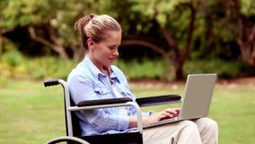 Ελκυστική γυναίκα σε μια αναπηρική καρέκλα που χρησιμοποιεί το lap-top της απόθεμα βίντεο