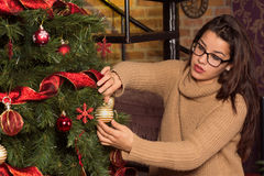 Ελκυστική γυναίκα στα γυαλιά που διακοσμεί το χριστουγεννιάτικο δέντρο Στοκ φωτογραφίες με δικαίωμα ελεύθερης χρήσης