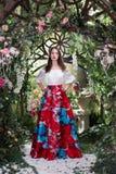 Ελκυστική γυναίκα στην κόκκινη φούστα στο floral κήπο Αφηρημένες ανασκοπήσεις φαντασίας με το μαγικό βιβλίο Στοκ φωτογραφίες με δικαίωμα ελεύθερης χρήσης