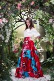 Ελκυστική γυναίκα στην κόκκινη φούστα στο floral κήπο Αφηρημένες ανασκοπήσεις φαντασίας με το μαγικό βιβλίο Στοκ Εικόνες