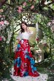 Ελκυστική γυναίκα στην κόκκινη φούστα στο floral κήπο Αφηρημένες ανασκοπήσεις φαντασίας με το μαγικό βιβλίο Στοκ εικόνες με δικαίωμα ελεύθερης χρήσης