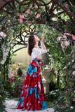 Ελκυστική γυναίκα στην κόκκινη φούστα στο floral κήπο Αφηρημένες ανασκοπήσεις φαντασίας με το μαγικό βιβλίο Στοκ Φωτογραφία
