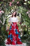 Ελκυστική γυναίκα στην κόκκινη φούστα στο floral κήπο Αφηρημένες ανασκοπήσεις φαντασίας με το μαγικό βιβλίο Στοκ εικόνα με δικαίωμα ελεύθερης χρήσης